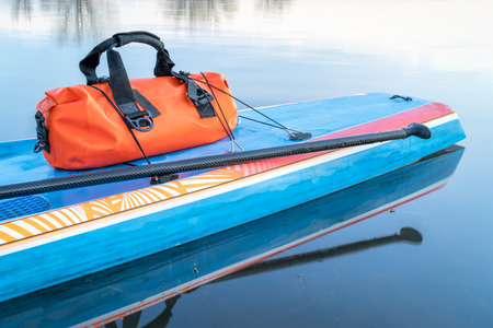 waterproof duffel on a deck of stand up paddleboard - paddling expedition concept
