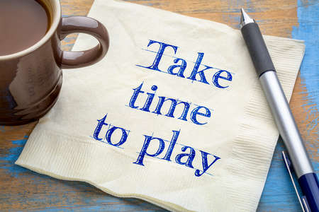 take time to play reminder - handwriting on a napkin with a cup of coffee