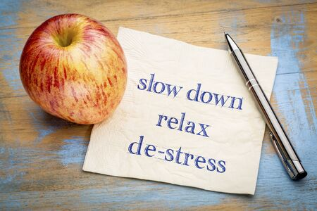 slow down, relax and de-stress - handwriting on a napkin with a fresh apple