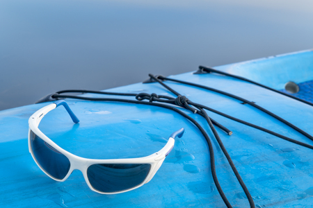 sport sunglasses on a wet deck of stand up paddleboard