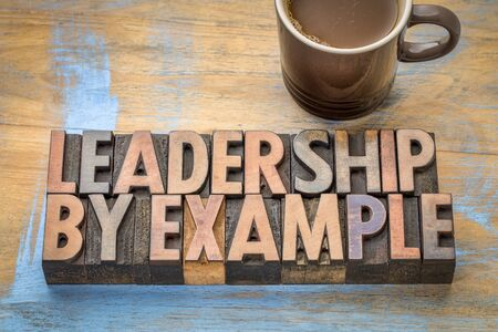 leadership by example - word abstract in vintage letterpress wood type with a cup of coffee