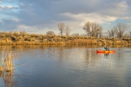 paddling a whitewater kayak on a calm lake in Colorado, early spring scenery Stock Photo