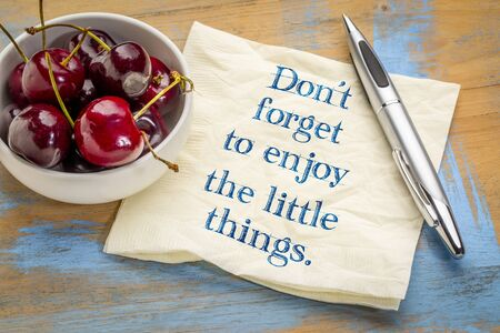 Do not forget to enjoy the little things - handwriting on a napkin with a bowl of cherries