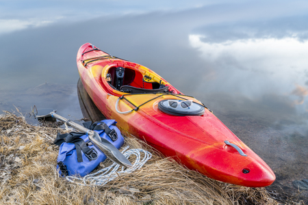 whitewater kayak on a lake shore with a paddle and waterproof duffel, early spring scenery in northern Colorado