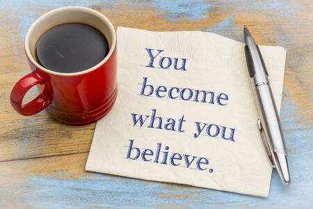 You become what you believe - handwriting on a napkin with a cup of espresso coffee Imagens