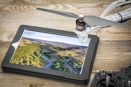 aerial photography concept - reviewing pictures of the Dismal RIver in Nebsrask on a digital tablet with a drone rotor and radio controller, screen picture copyright by the photographer Banque d'images