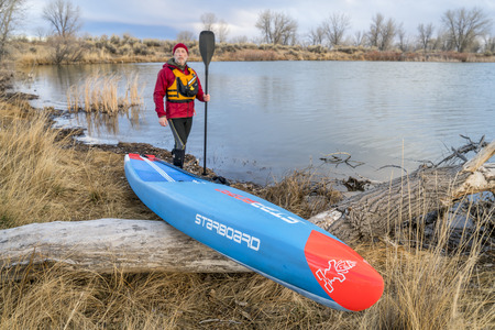 Fort Collins, CO, USA - March 19, 2018: The last winter paddling workout - a senior male paddler and his racing All Star stan up paddleboard (2018 model by Starboard) on a lake shore.