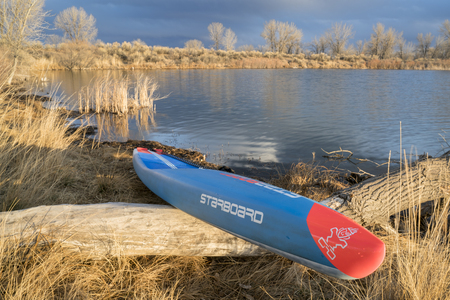 Fort Collins, CO, USA - March 19, 2018: Racing stand up paddleboard on a lake shore - 2018 model of All Star SUP by Starboard. Editöryel