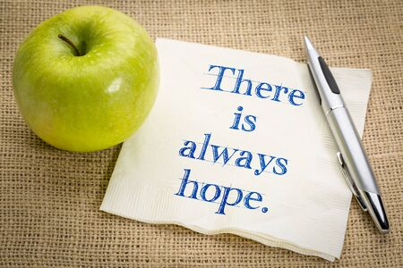 There is always hope. Handwriting on a napkin with a fresh apple. Banco de Imagens
