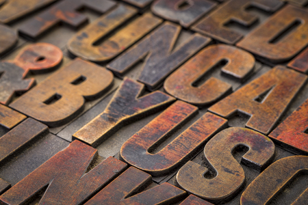 background of random vintage letterpress wood type printing blocks stained by color inks Stock Photo