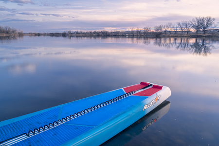 Fort Collins, CO, USA - March 21, 2018: Racing stand up paddleboard on a calm lake at dusk - 2018 model of All Star SUP by Starboard. Editöryel