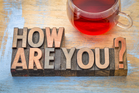 How are you? A word abstract in vintage letterpress wood type printing blocks with a cup of tea