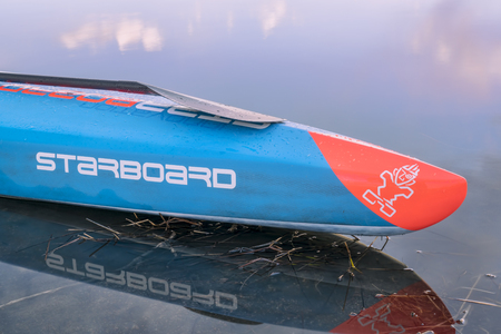 Fort Collins, CO, USA - March 17, 2018: Bow of acing stand up paddleboard on calm lake at dusk - 2018 model of All Star SUP by Starboard. Editöryel