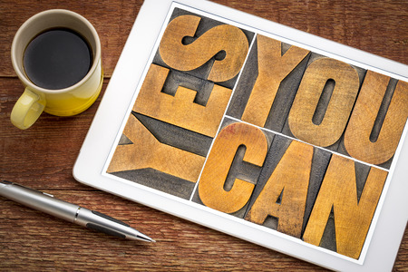 Yes you can - motivational slogan in vintage letterpress wood type on a digital tablet with a cup of coffee Stock Photo