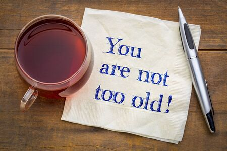 You are not too old! Positive affirmation, handwriting on a napkin  with a cup of tea.