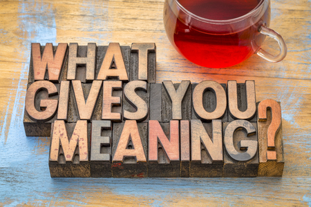 What gives you meaning? A question in vintage letterpress printing blocks with a cup of tea. Stock Photo