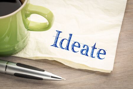 Ideate - form ideas, handwriting on napkin with a cup of tea