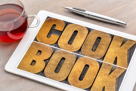 cookbook word abstract  - text in vintage letterpress wood type on a digital tablet with a cup of tea Stock Photo