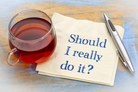 Should I reall do it ? A question in  handwriting on napkin with a cup of coffee