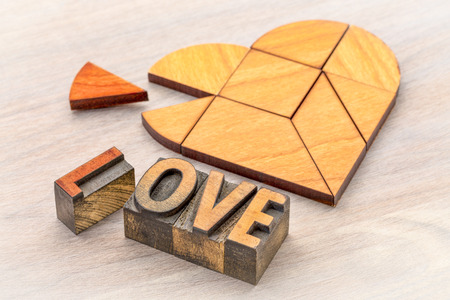 heart version of tangram puzzle with love word in vintage letterpress printing blcoks on grained wood