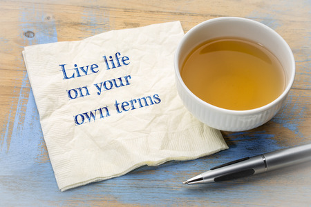 Live life on your own terms - inspirational handwriting on a napkin with a cup of tea