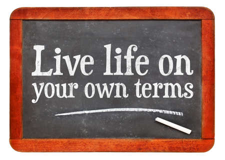 Live life on your own terms - white chalk text on a vintage slate blackboard Stock Photo