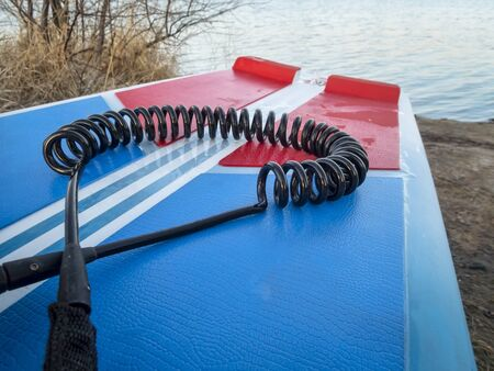 coil safety leash on a deck of stand up paddleboard - safety equipment Stock Photo