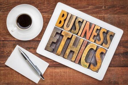 business ethics - word abstract in vintage letterpress wood type printing blocks on a digital tbalet with a cup of coffee