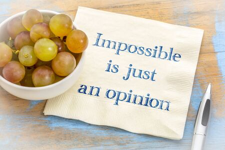 Impossible is just an opinion - inspirational handwriting on a napkin with fresh grapes