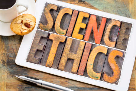 science ethics word abstract in vintage letterpress wood type printing blocks on a digital tablet with a cup of coffee