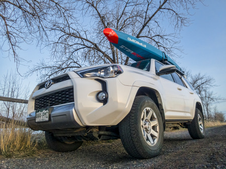 Fort Collins, CO, USA - APril 4, 2018: Toyota 4Runner SUV (2016 Trail edition) carrying a racing stand up paddleboard by Starboard on a lake shore, early spring scenery.