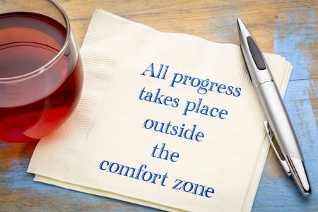 All progress takes place outside the comfort zone - inspiraitonal handwriting on a napkin with a cup of tea Stock Photo