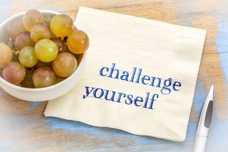 Challenge yourself  - motivational handwriting on a napkin with fresh grapes