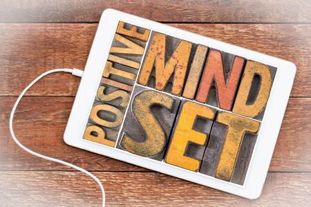 positive mindset word abstract in vintage letterpress wood type on a digital tablet
