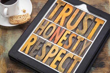 trust honesty, respect word abstract in vintage letterpress wood type on a digital tbalet with cup of coffee Stock Photo