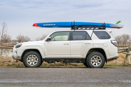 Fort Collins, CO, USA - April 7,2018: A racing stand up paddleboard by Starboard on roof racks of Toyota 4Runner (2016) SUV on a lake shore in one of city natural areas.