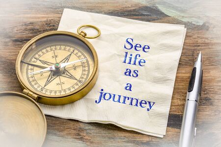 See life as a journey  - inspiraitonal handwriting on a napkin with an antique brass compass