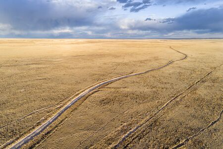 Dirt road winding through prairie in northern Colorado, early spring aerial view