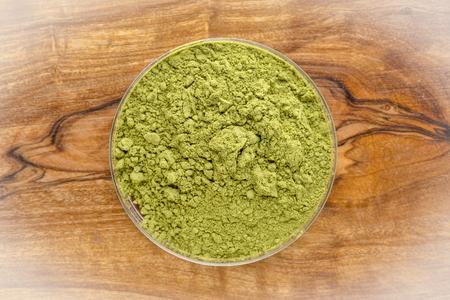 moringa leaf powder in around bowl agains olivetree wooden board