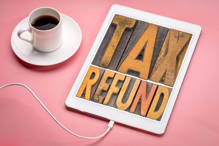 tax refund - word abstract in vintage letterpress printing blocks on a digital tablet with a cup of coffee