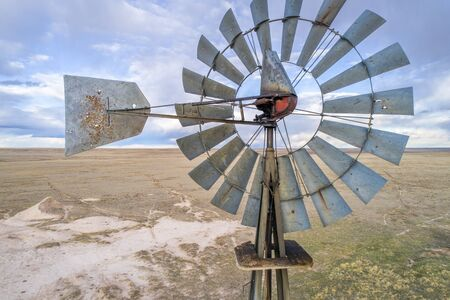 Close aerial view at old wind mill and water pump in prairie of northern COlorado