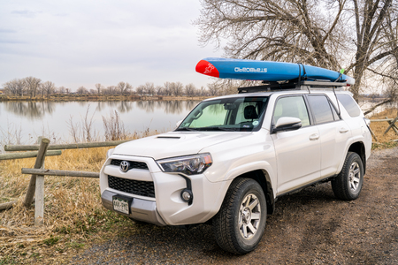 Fort Collins, CO, USA - April 7,2018: Toyota 4Runner SUV (2016 trail model) with a racing stand up paddleboard by Starboard on the lake shore.