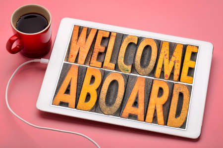 welcome aboard banner in vintage letterpress wood type blocks stained by color inks on a digital tablet with a cup of coffee
