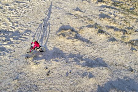 Riding a fat bike on a desert trail, aerial view with a long shadow Stock Photo