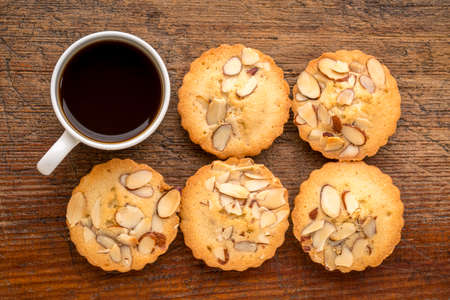 set of French almond cookies and espresso coffee against weathered  wood background Stock Photo