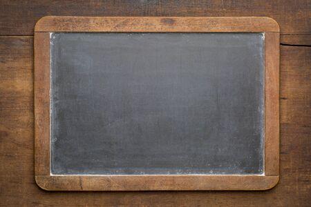 blank vintage slate blackboard against rustic grunge wood board Stock Photo