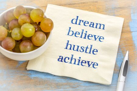 Dream, believe, hustle, achieve - inspirational handwriting on a napkin