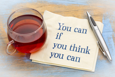 You can if think you can - inspirational handwriting on a napkin with a cup of tea