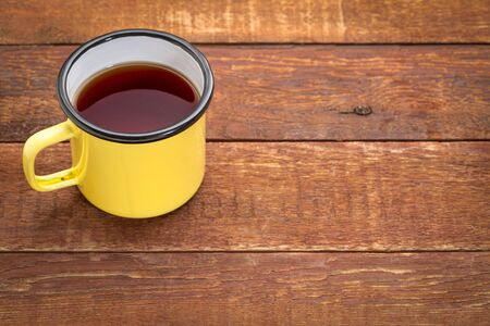 yellow metal enamel cup of hot tea on a rustic wooden picnic table with a copy space Stock Photo