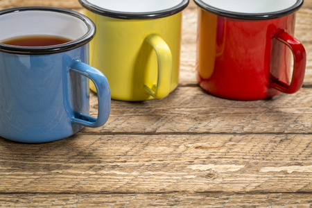 enamel metal cups of hot tea on a rustic wooden picnic table